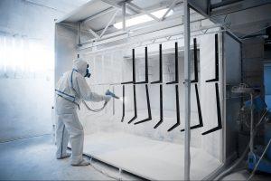 man powder coating in a powder coating booth